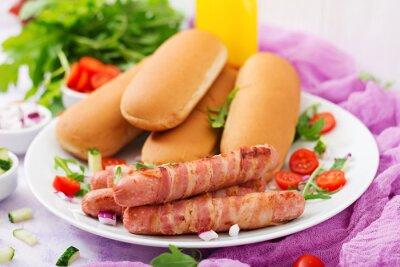 Składniki na gorący pies z kiełbasą. boczek, ogórek, pomidor i czerwona cebula na białej płytce