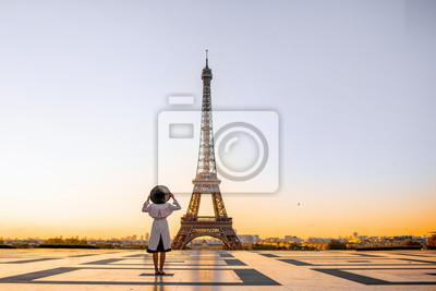 Plakat Słynny plac z pięknym widokiem na wieżę Eiffla i kobietę stojącą z tyłu, podziwiając widok na Paryż