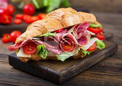 Smaczne śniadanie. Apetyczny croissant z salami i serem i pomidorami