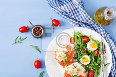 Smaczne śniadanie. Otwórz kanapki z łososiem, serem śmietankowym i chlebem żytnim w białym talerzu i sałatce z pomidorem, jajkiem i rukolą. Widok z góry. Leżał płasko
