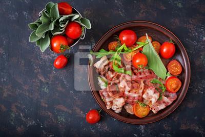 Smażony boczek i pomidory w płycie na ciemnym tle. Płaskie leże. Widok z góry.