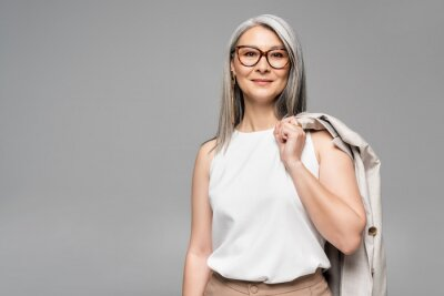 Plakat smiling asian businesswoman in eyeglasses isolated on grey