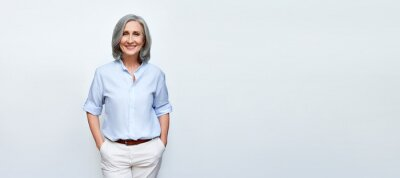 Plakat Smiling beautiful mature business woman standing isolated on white background. Older senior businesswoman, 60s grey haired lady professional female ceo, coach looking at camera, banner, copy space.