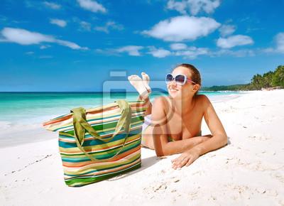 Smiling beautiful woman sunbathing on a beach