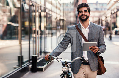 Plakat Smiling businessman using tablet on the way to office. Business, education, lifestyle concept