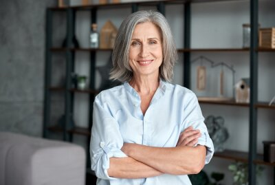 Plakat Smiling confident stylish mature middle aged woman standing at home office. Old senior businesswoman, 60s gray-haired lady executive business leader manager looking at camera arms crossed, portrait.