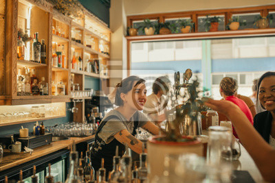 Plakat Smiling female bartender talking with customers at a bar counter