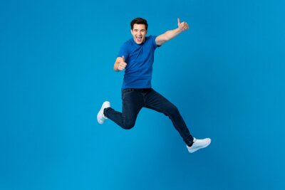 Plakat Smiling handsome American man joyfully jumping and doing double thumbs up gesture isolated on blue studio background