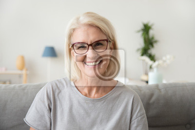 Plakat Smiling middle aged mature grey haired woman looking at camera, happy old lady in glasses posing at home indoor, positive single senior retired female sitting on sofa in living room headshot portrait