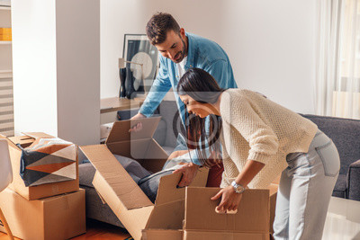 Plakat Smiling young couple move into a new home carrying boxes of belongings.