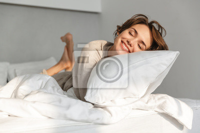 Plakat Smiling young girl relaxing in bed