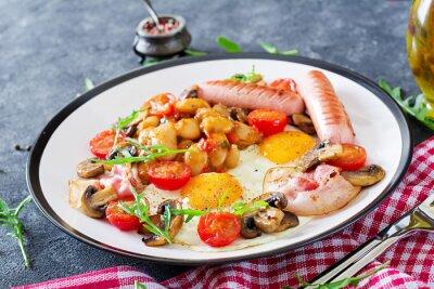 Śniadanie angielskie - jajko sadzone, fasola, pomidory, pieczarki, boczek i kiełbasa. Smaczne jedzenie.