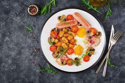 Śniadanie angielskie - jajko sadzone, fasola, pomidory, pieczarki, boczek i kiełbasa. Smaczne jedzenie. Widok z góry. Płaskie leżało.
