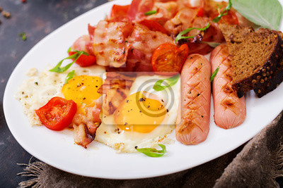 Śniadanie angielskie - jajko smażone, kiełbasa, pomidory, boczek i tosty.