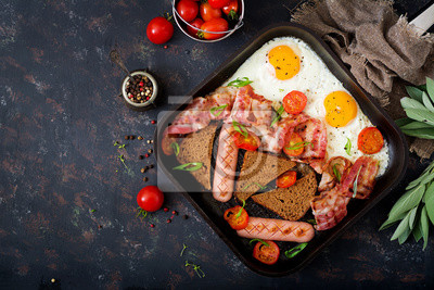 Śniadanie angielskie - jajko smażone, kiełbasa, pomidory, boczek i tosty. Widok z góry. Płaskie leże