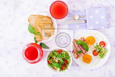Śniadanie angielskie - jajko smażone, pomidory i boczek. Płaskie leże. Widok z góry