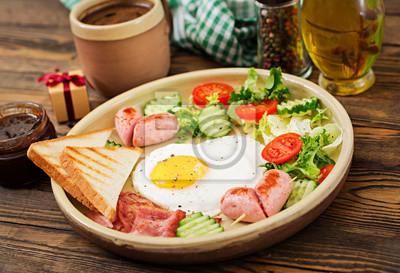 Śniadanie na Walentynki - jajko sadzone w kształcie serca, grzanki, kiełbasa, boczek i świeże warzywa. angielskie śniadanie