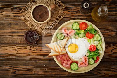 Śniadanie na Walentynki - jajko sadzone w kształcie serca, grzanki, kiełbasa, boczek i świeże warzywa. Angielskie śniadanie. Kubek kawy. Widok z góry