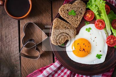 Śniadanie na Walentynki - smażone jajka i chleb w kształcie serca i świeżych warzyw. Widok z góry