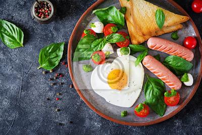 Śniadanie na Walentynki - smażone jajka w kształcie serca, kiełbasa, tosty i caprese sałatka z pomidorów, bazylii i mozzarelli. Domowe, smaczne jedzenie. Widok z góry. Płaskie leżało