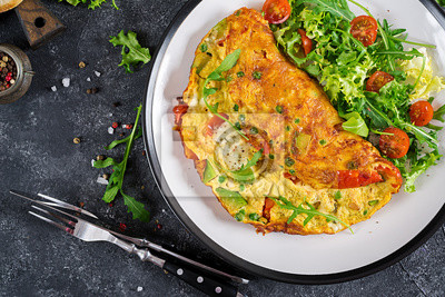 Śniadanie. Omlet z pomidorami, awokado, serem pleśniowym i zielonym groszkiem na białym talerzu. Frittata - włoski omlet. Widok z góry