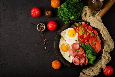Śniadanie. Smażący jajka z kiełbasą i warzywami w smaży niecce na czarnym tle w wieśniaku projektują. Widok z góry