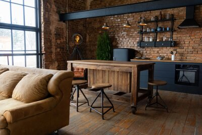 Plakat Spacious industrial loft kitchen and living room with big windows, brown sofa and black cabinets