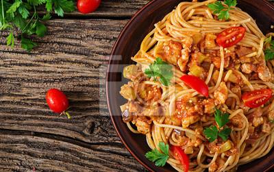 Spaghetti Bolognese makaron z pomidorowym kumberlandem, warzywami i minced mięsem, - domowej roboty zdrowy włoski makaron na nieociosanym drewnianym tle. Widok z góry. Leżał płasko