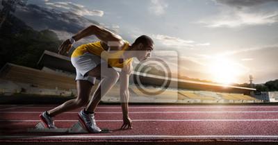 Plakat Sport. Sprinter opuszczania bloków zaczynając na bieżni.