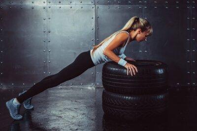 Plakat Sportsmenka. Nadające sportowy sportowiec kobieta robi push up na opony