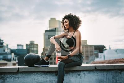 Plakat Sprawności fizycznej kobiety obsiadanie na dachu bierze przerwę od treningu