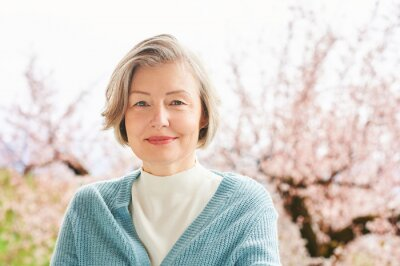 Plakat Spring portrait of beautiful and elegant middle age woman posing against pink blooming tree