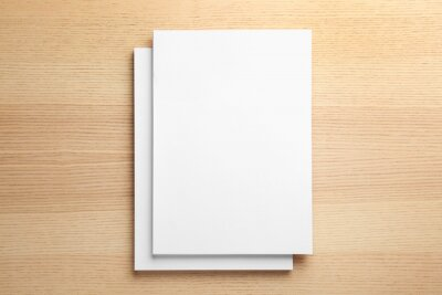Plakat Stack of blank paper sheets for brochure on wooden background, top view. Mock up