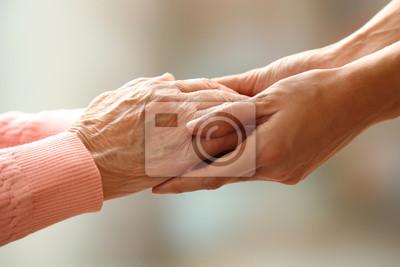 Plakat Stare i młode trzymając się za ręce na jasnym tle, z bliska