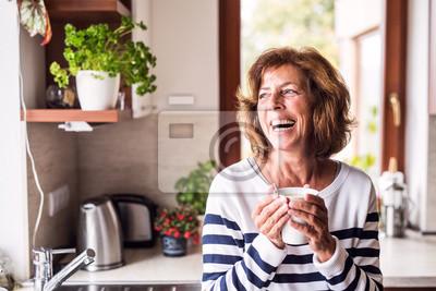 Plakat Starsza kobieta trzyma filiżankę kawy w kuchni.