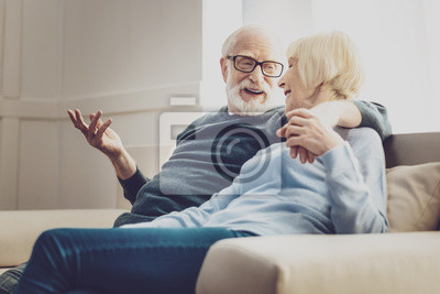 Plakat Starsza para. Radosna starsza kobieta patrząc na swojego ukochanego mężczyznę słuchając jego żartów
