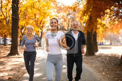 Plakat Starszy mężczyzna i kobieta i młody żeński instruktor trening na świeżym powietrzu. Zajęcia na świeżym powietrzu, zdrowy styl życia, silne ciała, pasujące figury. Stylowa, nowoczesna odzież sportowa.