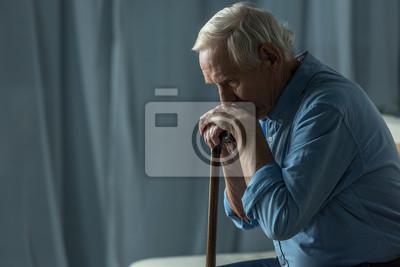 Plakat Starszy smutny mężczyzna opiera na trzcinie podczas gdy siedzący na kanapie