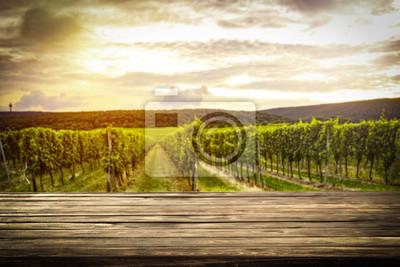 Plakat stary rustykalny stół w pięknej winnicy o zachodzie słońca