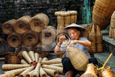 Plakat Stary wietnamski żeński rzemieślnik robi tradycyjnemu bambusowi rybi oklepiec lub wyplata przy starym tradycyjnym domem w Thu sy handlu wiosce, Wieszający jen, Wietnam, tradycyjny artysty pojęcie