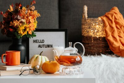 Plakat Still-life. A blanket, pumpkins, a teapot and a cup of tea on the coffee table in the home interior of the living room. A cozy autumn concept.