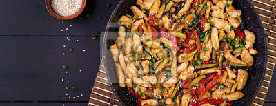 Stir fry chicken, zucchini, sweet peppers and green onion. Top view. Banner. Asian cuisine