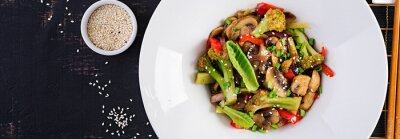 Stir fry vegetables with mushrooms, paprika, red onions and broccoli. Healthy food. Asian cuisine. Top view, banner