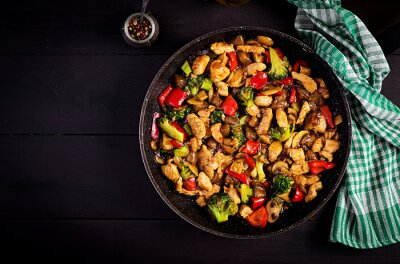 Stir fry with chicken, mushrooms, broccoli and peppers. Chinese food. Top view, overhead