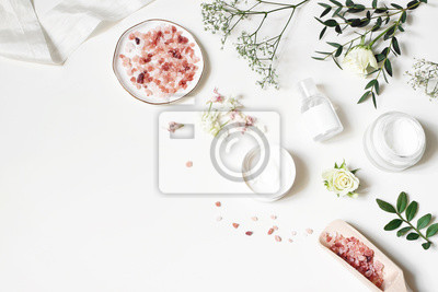Plakat Styled beauty corner, web banner. Skin cream, tonicum bottle, dry flowers, leaves, rose and Himalayan salt. White table background. Organic cosmetics, spa concept. Empty space, flat lay, top view.