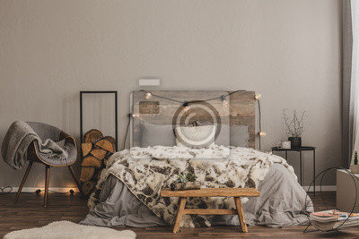 Plakat Stylish grey chair with blanket and log of wood next to warm double bed with wooden headboard and light bulbs