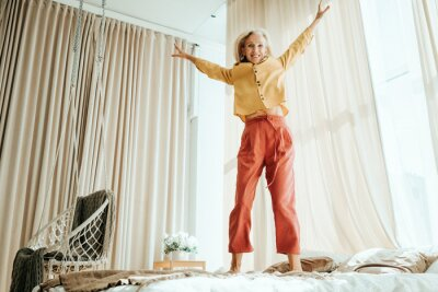 Plakat Stylish mature woman at her cozy home apartment. Energy jumping on the bed