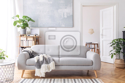 Plakat Stylish scandianvian living room with design sofa with elegant blanket, coffee table and bookstand on the white wall. Brown wooden parquet. Concept of minimalistic decor interior with piano. Mock up.
