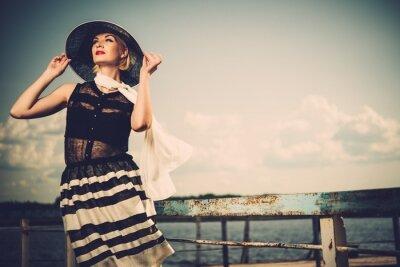 Plakat Stylowa piękna kobieta na starym molo
