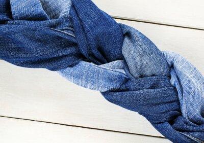 stylowe i skręcone warkocze tkane z różnych blue jeans na białym drewnianym stole